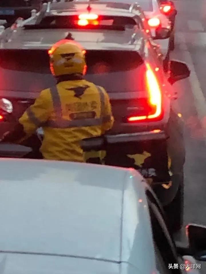 消防车正在等红绿灯时,一外卖小哥突然向车内塞进了两块蛋糕