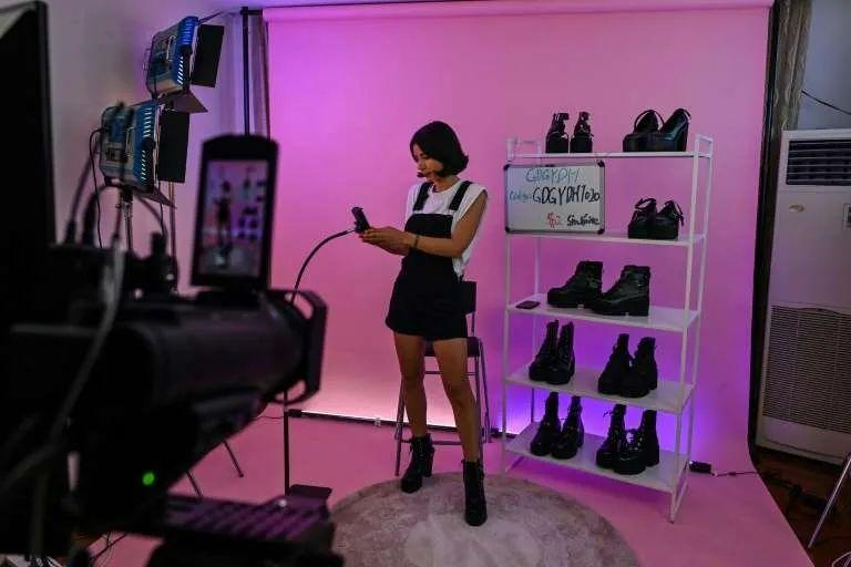 ▲一位女主播正在直播卖鞋。(图片来源:法新社)