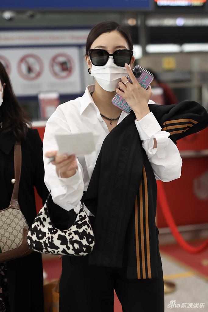 宋妍霏穿白衬衫搭侧空长裤拎奶牛纹小包造型时髦干练