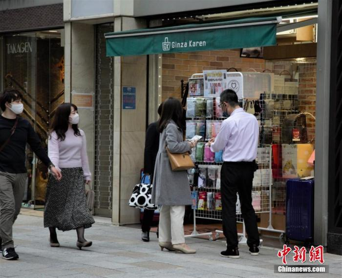 原料图:东京民多在商店购买口罩。 中新社记者 吕少威 摄
