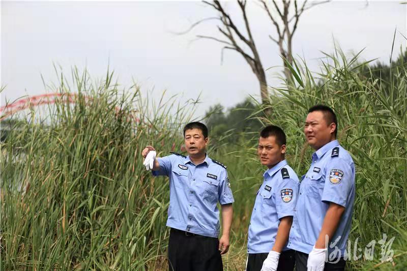 图为张岩(左)在一首案发现场指挥案情。秦皇岛市公安局供图
