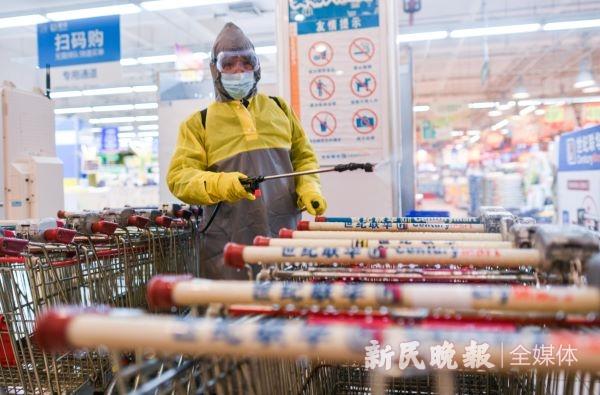 图说:昨晚十点,仙霞路上一家超市结束营业,工作人员对购物车进行消毒 新民晚报记者 陈梦泽 摄