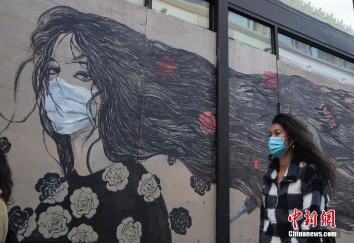 当地时间11月21日,美国加州旧金山市民戴口罩出行。中新社记者 刘关关 摄