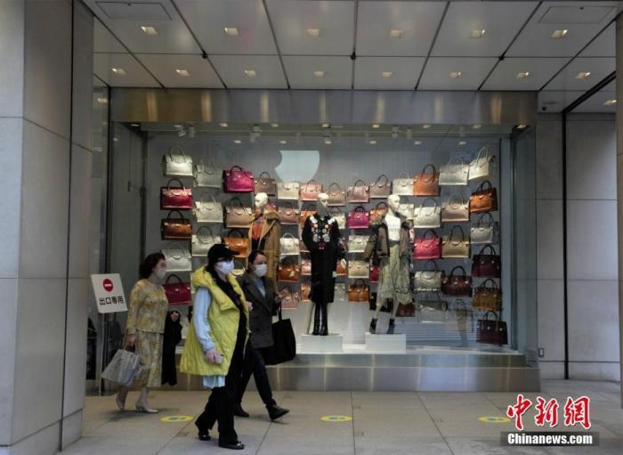 近期日本疫情有反弹趋势。图为东京民众经过商场橱窗。 中新社记者 吕少威 摄