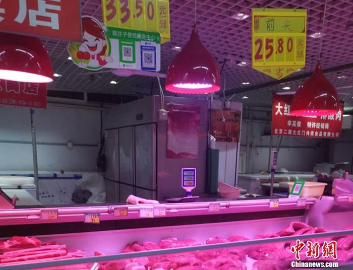图为北京丰台区一家菜市场内的猪肉摊。 谢艺观 摄