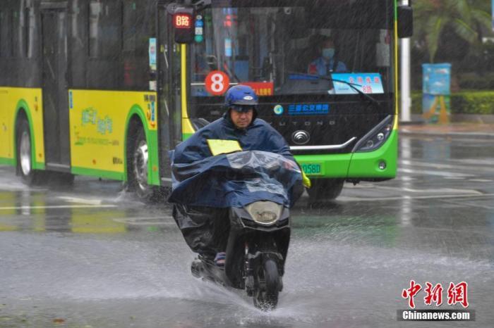 质料图:市民在风雨中出行。 中新社记者 骆云飞 摄