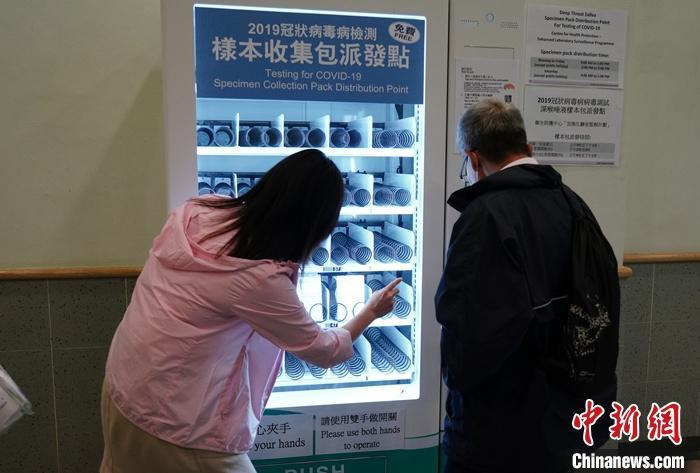 """原料图:有市民在香港西湾河清淡科门诊诊所的检测样本搜集包""""自动派发机""""上自立领取样本包。 中新社记者 张炜 摄"""