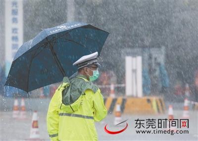 ▲2月15日,大雨滂沱,在广深高速南城石鼓出入口说相符检疫站,执勤民警撑着雨伞在雨中坚守岗位