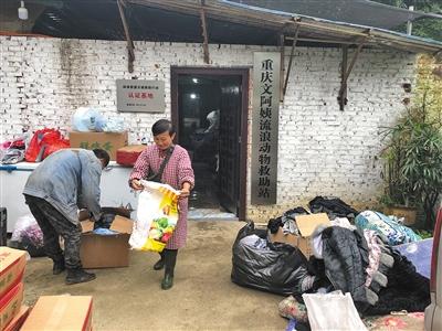 文军红和工人在修整善心人送来的旧衣服。二十年间,文军红救下上千只漂泊猫狗,成为重庆市著名的漂泊动物援助人,创建了当地周围数一数二的幼我漂泊动物援助站。