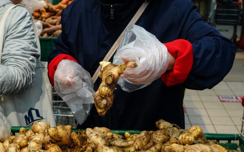 11月14日,物美超市惠新店,有顾客购买商品时不想弄脏手,就将连卷袋当成了手套。摄影/新京报记者李凯祥