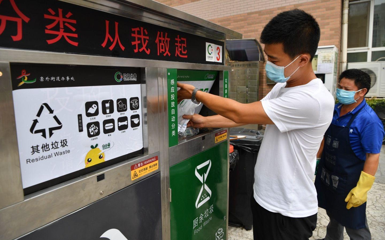 7月30日,东城区新世界家园,居民将一袋厨余垃圾投入装有破袋器的垃圾桶。破袋器会打破塑料袋,倾倒垃圾,再将塑料袋转入其他垃圾桶。摄影/新京报记者 吴江