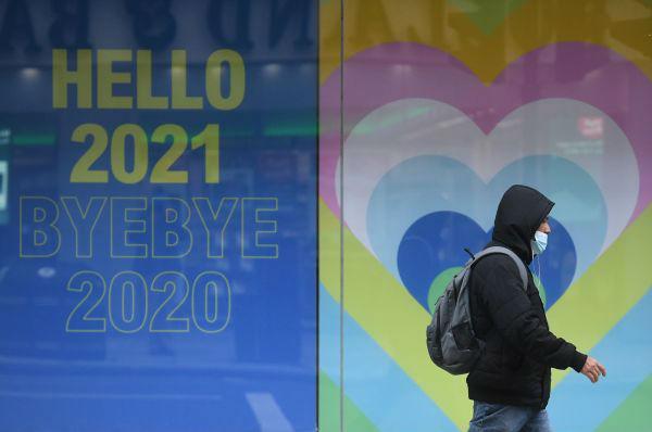 12月26日,一名戴口罩的男子从伦敦街头的新年海报前经过。(欧新社)