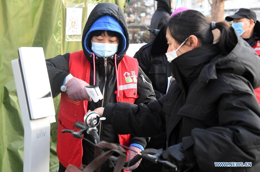 A community worker (L) measures body temperature for a resident at the entrance of the Hongcheng Huayuan residential compound on Wangquan Street, Shunyi District, Beijing, capital of China, on Dec. 29, 2020. Beijing reported seven new locally-transmitted confirmed COVID-19 cases on Monday, according to the Beijing municipal health commission. The seven patients, who live in the Shunyi District, are all close contacts of earlier reported cases. (Xinhua/Ren Chao)
