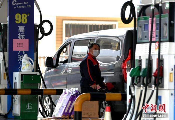 图为加油站工作人员在工作。中新社记者 王东明 摄