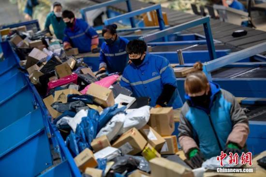 资料图:快递企业员工分拣包裹。中新社记者 韦亮 摄