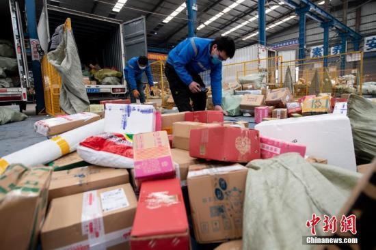 原料图:2月20日,山西省太原市,在中通快递山西转运中央,员工戴着口罩分拣包裹。中新社记者 韦亮 摄