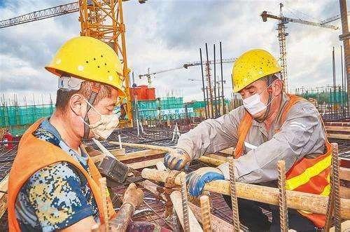建筑工人戴着口罩在工地作业