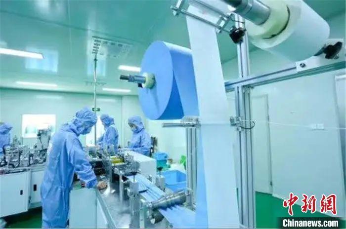 图为生产线上工人正在生产口罩。王将 摄