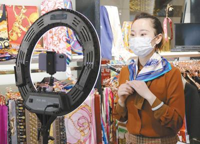 近日,北京秀水街大厦复工开业,图为一位经营者通过手机直播销售商品。