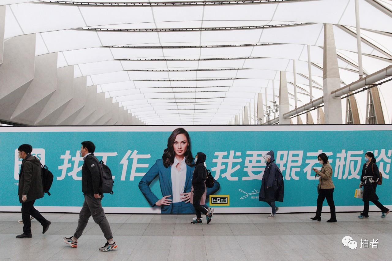 △3月24日,西二旗地铁站,乘客走过站内招聘广告牌。