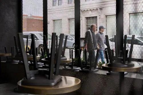 ▲3月20日,在美国加利福尼亚州洛杉矶,人们经过星光大道上一家停业的餐馆。新华社发(钱卫忠 摄)