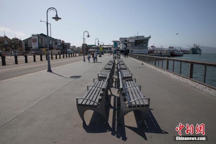 当地时间4月12日,美国旧金山市民在渔人码头附近散步。针对新冠肺炎疫情的出行禁令颁布之后,这里比平时冷清了许多。 中新社记者 刘关关 摄