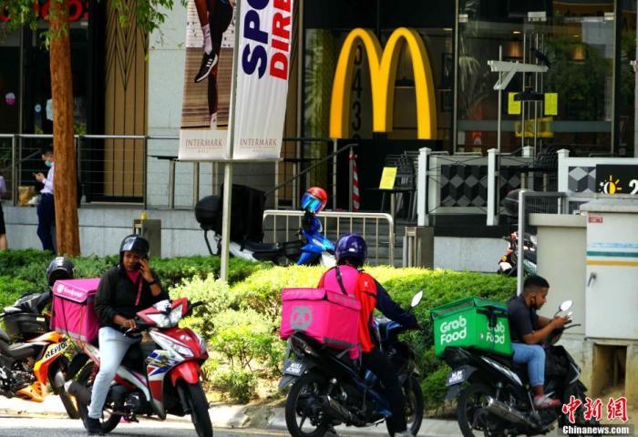 """当地时间3月18日,马来西亚当局正式最先实走""""走动节制令"""",关闭大片面当局机构、私营企业和商场及宗教场所。请求民多尽量留在家中。外卖顿时成为不少马来西亚民多选择。 陈悦 摄"""