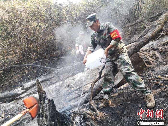 4月1日,扑火人员正在清理烟点。西昌市委宣传部供图