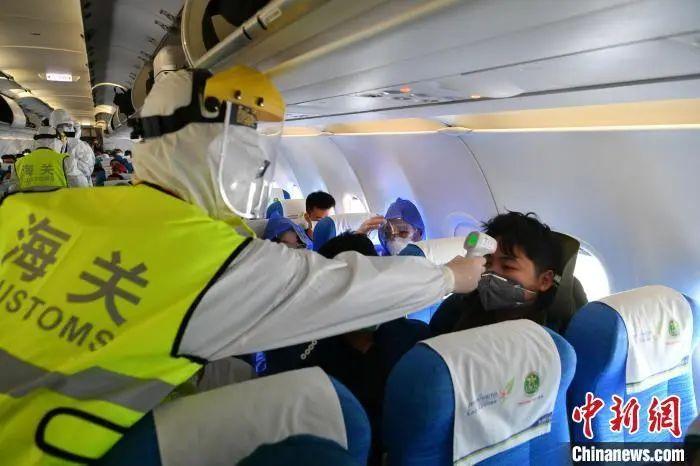 资料图:工作人员为入境旅客测量体温。刘冉阳 摄