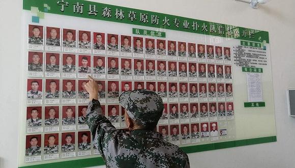 扑火队81名队员的照片墙。摄影:赵孟