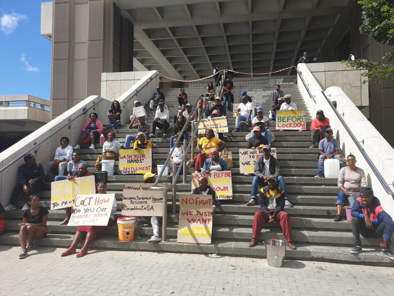 图五。全境封锁的消息宣布之后,40名开普敦Khayelitsha棚户区居民在市政厅台阶上以一米的距离抗议,要求政府在实施全国封禁措施前提供饮用水。图片来源:Mary-Anne Gontsana