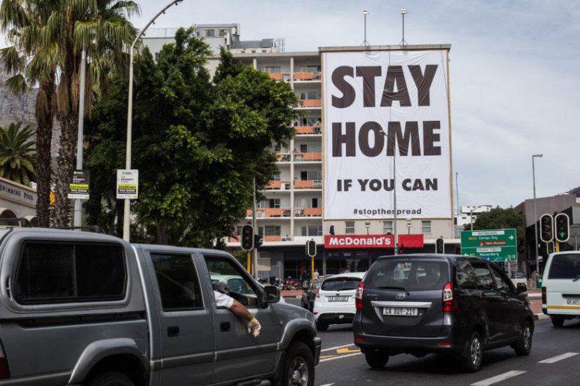 图二。 南非城市开普敦长街打出鼓励市民尽量居家、不外出的标语。图片来源:Ashraf Hendricks