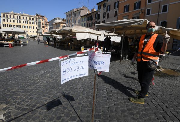 4月6日,在意大利首都罗马,一位工作人员在一个市场的入口控制顾客人数。(新华社)