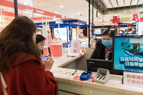 2月10日,在长沙王府井百货商场,消耗者在收银台买单。 新华社发