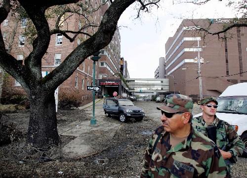 """2005年9月13日,美国路易斯安那州新奥尔良市,两名军人在""""卡特里娜""""飓风灾区的一个医疗中心前警戒。"""