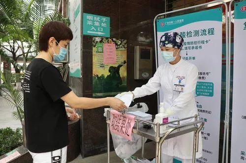 5月15日,广州市第一人民医院,医务人员将筹备好的核酸检测功效递给被检测人。记者洪泽华摄