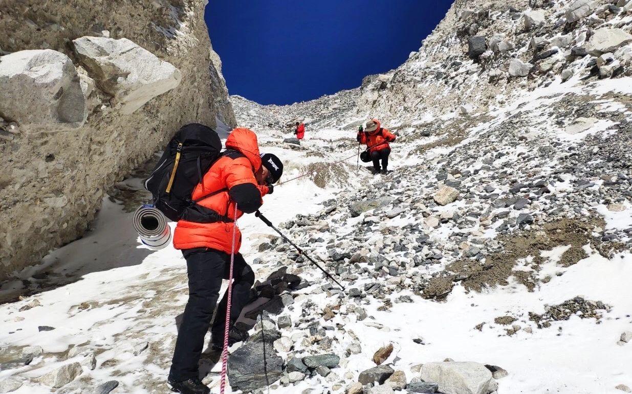 测绘队员背着防潮垫,爬上陡坡,前往测绘地点。受访者供图