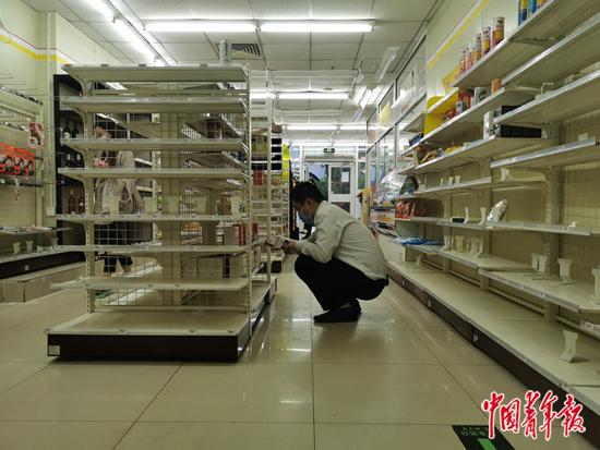 5月12日下午,在北京全时(万达广场店),店内商品几乎被抢光了,一位男士正蹲在地上研究一款茶叶。中青报·中青网见习记者赵丽梅/摄