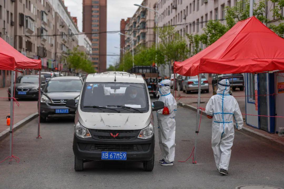 5月18日,在舒兰市某小区,工作人员为出入居民测温登记。