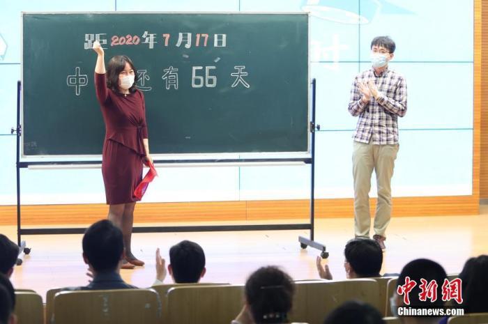 资料图:5月11日,在位于北京市西城区的北京师范大学附属实验中学内,教师代表为中考倒计时牌揭幕。当日,北京初三年级学生返校复课。 中新社记者 蒋启明 摄