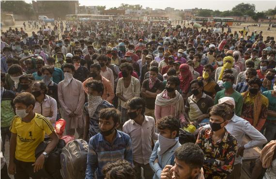 5月18日,在印度新德里郊区的添济阿巴德新闻资讯,准备返乡的农民工列队期待登车。 新华社 图