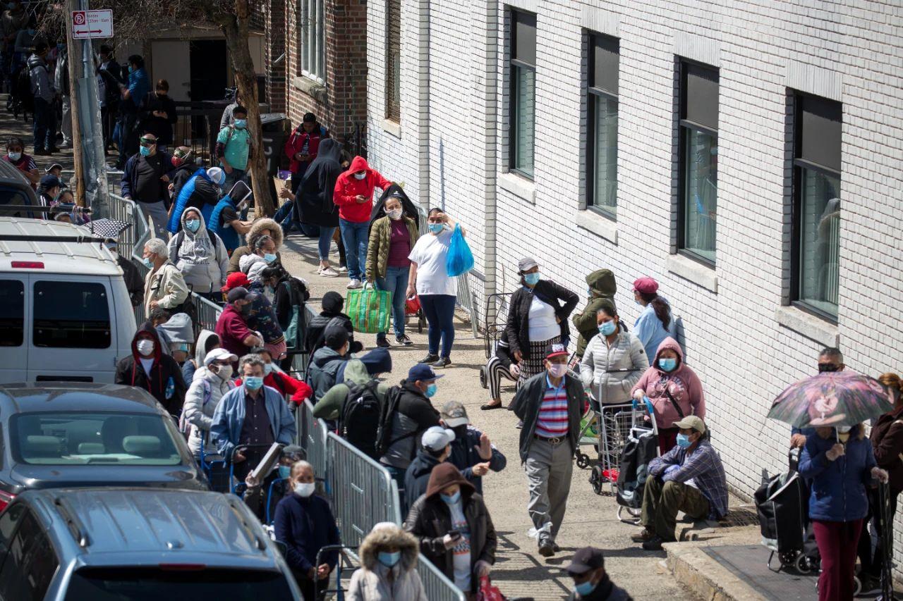 在美國紐約一個食品發放點,人們排隊等待領取慈善組織發放的免費食品。新華社圖