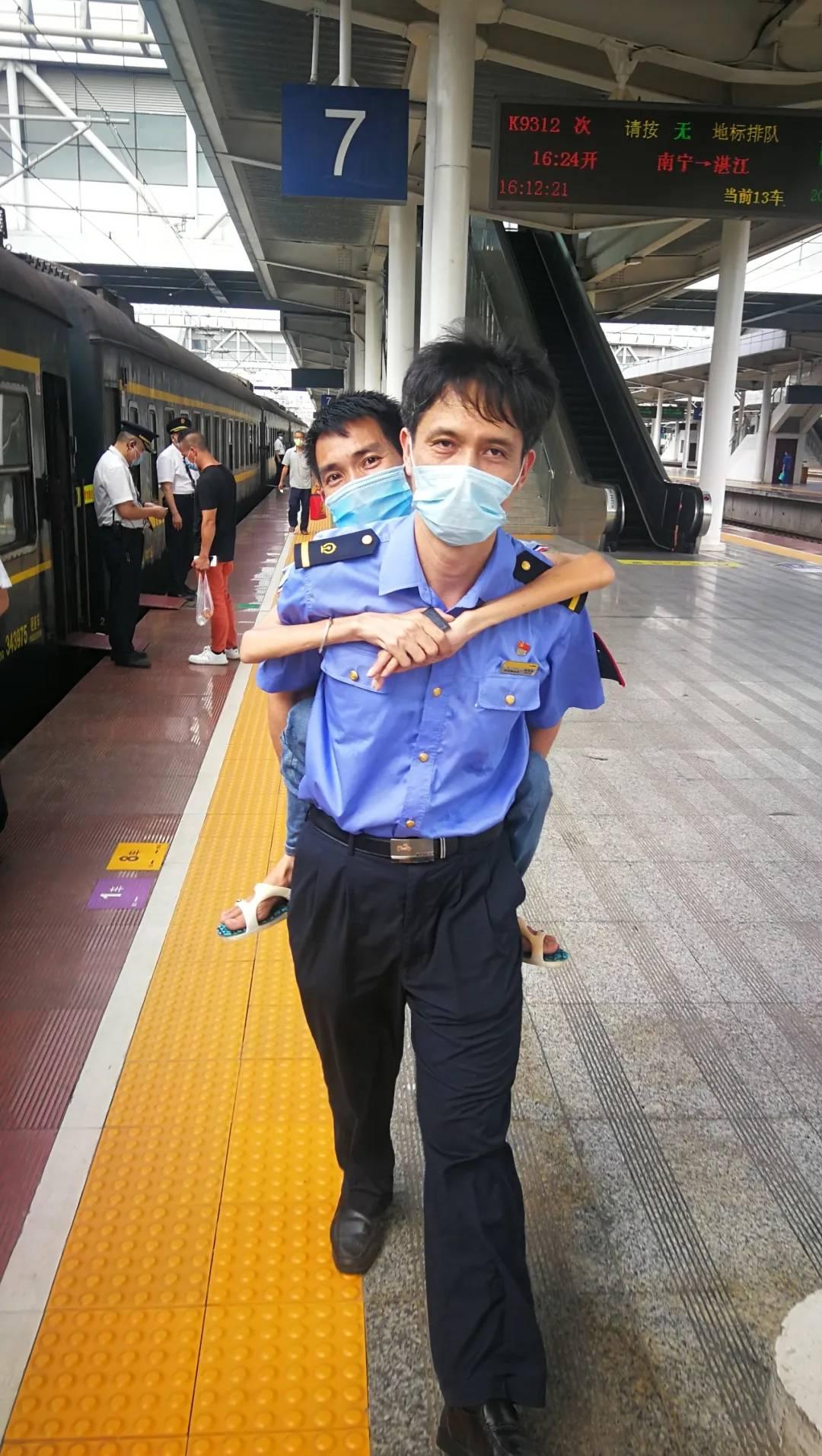 南宁火车站工作人员主动背腿脚不便旅客送他上车