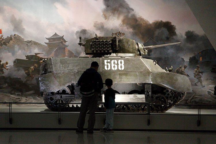 """观众参观美国造M3A3斯图亚特轻型坦克。1948年,该坦克参加济南战役,炮手沈许勇敢作战,出色完成任务,为此,沈许被誉为""""铁人""""英雄,该坦克被授予""""功勋坦克""""称号。"""