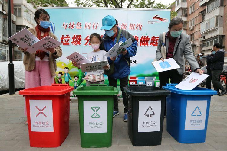 居民将手中的垃圾图卡别离投放到四色垃圾桶内。