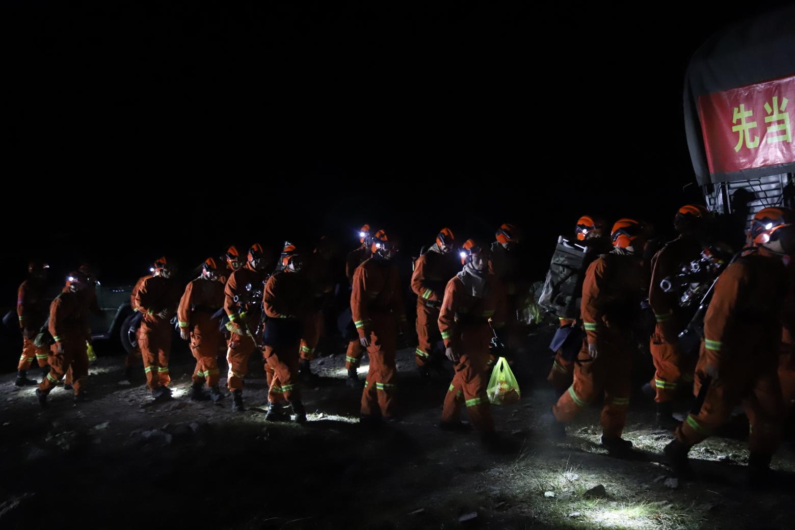 9日早晨4点,阿坝森林消防支队的指战员背着熄灭装备向火场挨近。 阿坝森林消防支队报道员卢耀强/摄