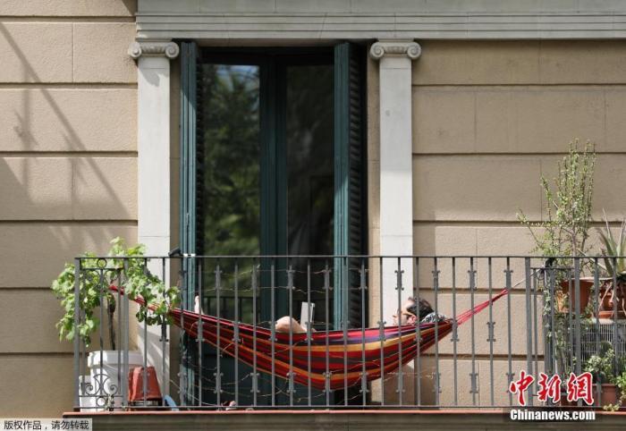 当地时间4月10日,西班牙巴塞罗那,居家令下,居民在阳台上享福晴天气。
