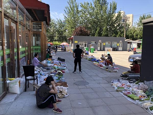 松榆东里市场室内商铺区域仍然关闭,有商贩临时在室外摆摊。澎湃新闻记者 汤琪 图