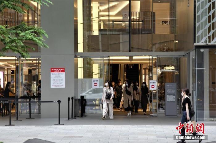 当地时间6月6日,日本东京民众戴口罩走出商场。中新社记者 吕少威 摄
