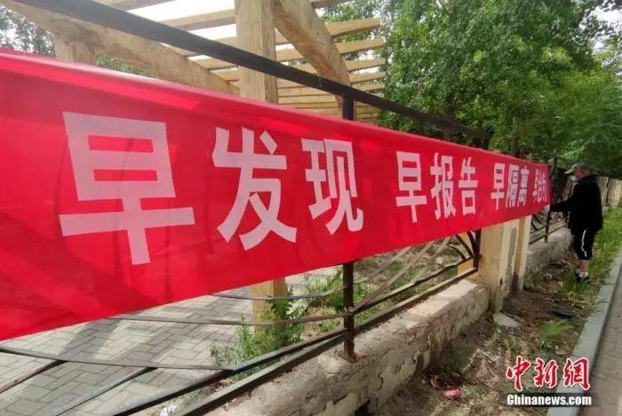 6月16日,北京花乡地区一街道边,工作人员正在悬挂防疫宣传横幅。中新社记者 张宇 摄